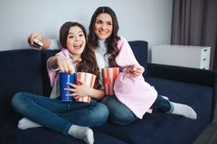 Beautiful brunette caucasian mother and daughter sit together in room. Emotional excited girl point forward. She hold stock image