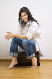 Beautiful brunette sitting on the coffer. Royalty Free Stock Photography
