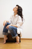 Beautiful brunette sitting on the coffer. Royalty Free Stock Images