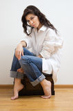 Beautiful brunette sitting on the coffer. Stock Images