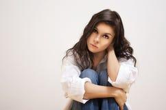 Beautiful brunette sitting on the floor. Stock Photos
