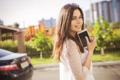 Beautiful brunette caucasian young woman standing near black car Royalty Free Stock Photo