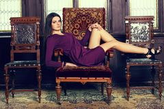 Beautiful brunette on the chateau chair. Beautiful brunette in violet gown lying on the chateau chair, indoors, chateau environment, fashion photo, studio Stock Images