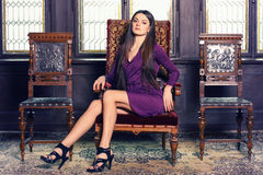 Beautiful brunette on the chateau chair. Beautiful brunette in violet gown sitting on the chateau chair, indoors, chateau environment, fashion photography Royalty Free Stock Photos
