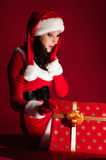 Beautiful brunette in Christmas dress opens gift Royalty Free Stock Photography