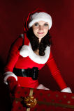 Beautiful brunette in Christmas dress opens gift. Stock Image
