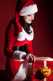 Beautiful brunette in Christmas dress opens gift Royalty Free Stock Images