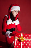 Beautiful brunette in Christmas dress opens gift. Stock Photos