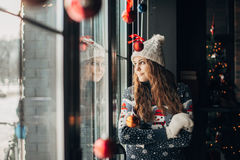 Beautiful brunette in Christmas sweater looking out the window. Girl in a cap looking out the window,Christmas.new year.Christmas photo shoot stock images