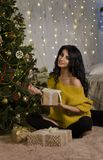 Beautiful brunette with a Christmas tree and a gift Royalty Free Stock Photography