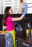 Beautiful brunette cleans the kitchen furniture Stock Images