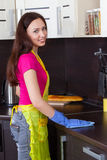 Beautiful brunette cleans the kitchen furniture Stock Photography