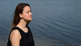 Beautiful brunette with closed eyes and in a black shirt; enjoying by the coast. A beautiful brunette with closed eyes and in a black shirt;enjoying by the coast stock video footage