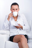Beautiful brunette at coffee break. On the sofa Stock Images