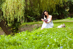 Beautiful brunette country girl reading a book near the river Stock Images