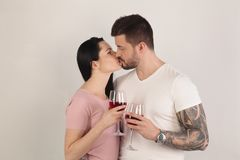 Beautiful brunette couple drink wine and kissing in front of a white background. A man with a cool tattoo on hand royalty free stock image