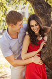 Beautiful brunette couple in love hugging on a date in the park. Stock Photo