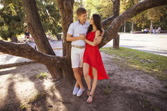 Beautiful brunette couple in love hugging on a date in the park. Royalty Free Stock Images