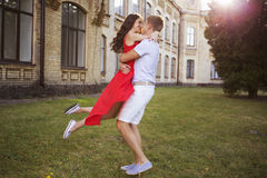 Beautiful brunette couple in love hugging on a date in the park. Royalty Free Stock Image