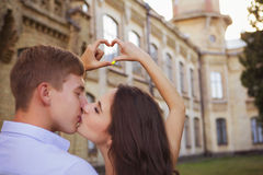 Beautiful brunette couple in love kissing on a date in the park, Stock Photography