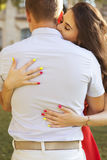 Beautiful brunette couple in love kissing on a date in the park. Royalty Free Stock Photos