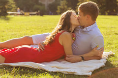 Beautiful brunette couple in love kissing on a date in the park. Stock Photo