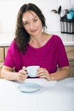 Beautiful brunette with cup of coffee in kitchen Stock Images