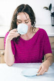 Beautiful brunette with cup of coffee in kitchen Royalty Free Stock Image