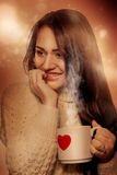 Beautiful brunette with cup of tea looking away in studio Royalty Free Stock Image