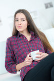 Beautiful brunette with cup tea on sofa Stock Photos