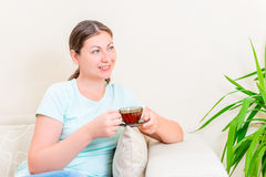Beautiful brunette with a cup of tea on a sofa Royalty Free Stock Photos