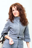 Beautiful brunette with curly hair standing with a bag in hand Royalty Free Stock Photo