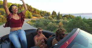 Beautiful brunette dancing while sitting on hood of convertible stock video footage