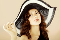 Beautiful brunette in the dark dress swimsuit and the hat Stock Photography