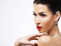Beautiful brunette with dark makeup wearing blue jewellery Stock Photography