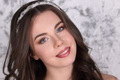 Beautiful brunette in diadem and with hairdo. Smiles in studio, close-up Royalty Free Stock Images