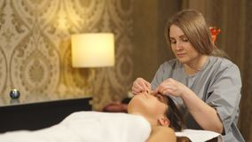Beautiful brunette doing a facial massage in a Spa center stock footage