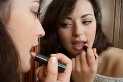 Beautiful brunette doing make-up Stock Image