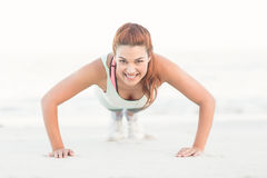 Beautiful brunette doing push ups royalty free stock photography