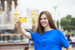 Beautiful brunette dress taking pictures of herself on a cellpho Royalty Free Stock Photos
