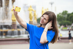 Beautiful brunette dress taking pictures of herself on a cellpho Royalty Free Stock Photography