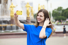 Beautiful brunette dress taking pictures of herself on a cellpho Stock Photo