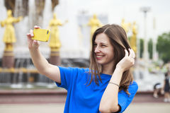 Beautiful brunette dress taking pictures of herself on a cellpho Stock Image