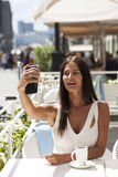 Beautiful brunette dress taking pictures of herself on a cellpho. Young beautiful brunette dress taking pictures of herself on a cellphone sitting in a summer Stock Images