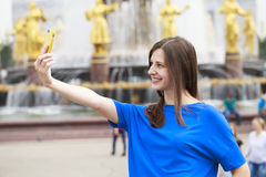 Beautiful Brunette Dress Taking Pictures Of Herself On A Cellphone In A City Park Stock Photos