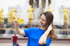 Beautiful Brunette Dress Taking Pictures Of Herself On A Cellphone In A City Park Stock Photo