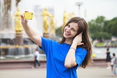 Beautiful Brunette Dress Taking Pictures Of Herself On A Cellphone In A City Park Royalty Free Stock Photography