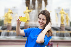 Beautiful Brunette Dress Taking Pictures Of Herself On A Cellphone In A City Park Stock Images