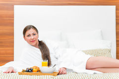 Beautiful brunette in a dressing gown with a meal Royalty Free Stock Image
