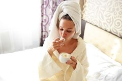 Beautiful brunette in a dressing gown and a sweatshirt on her head is having breakfast in bed stock photo